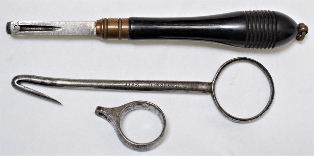 Three early simple pinfire extractors. From top to bottom: an ebony handled tool possible a copy of the early French pattern, a steel extractor stamped with the makers name Dixon & Sons and catalogue number 1132 and a ring extractor.n